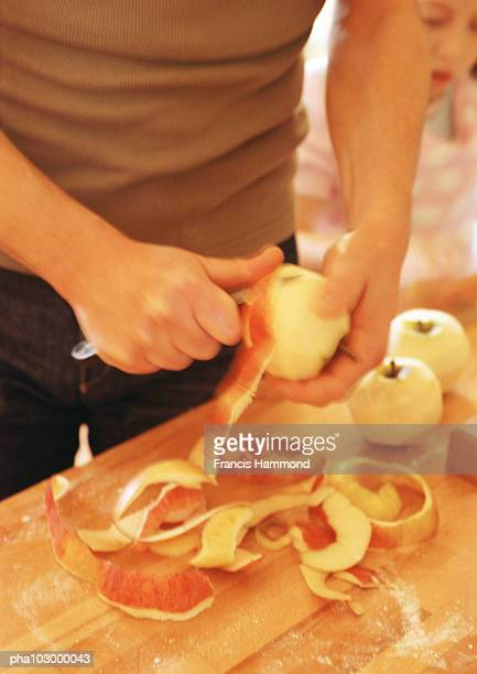 Hands peeling apples