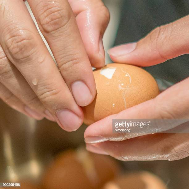 Hands Peeling Boiled Eggs.