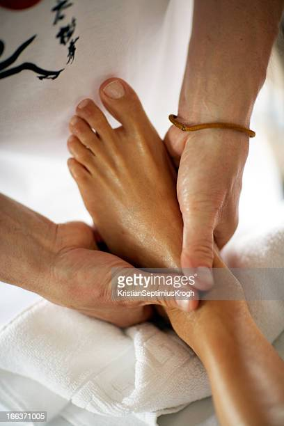 hands perform reflexology on a foot - foot massage stock pictures, royalty-free photos & images