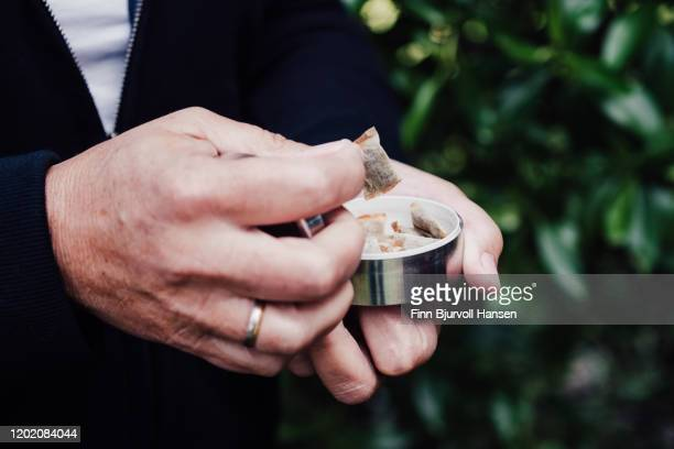 hands picking up a portion of snuff, snus nicotin pad from the box - finn bjurvoll stock-fotos und bilder