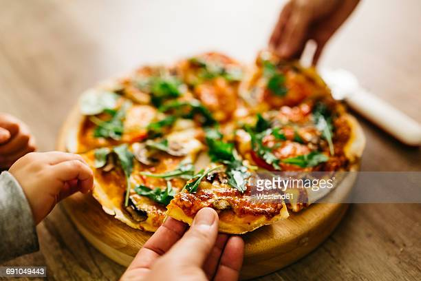 hands picking up pizza slices - homemade stock pictures, royalty-free photos & images
