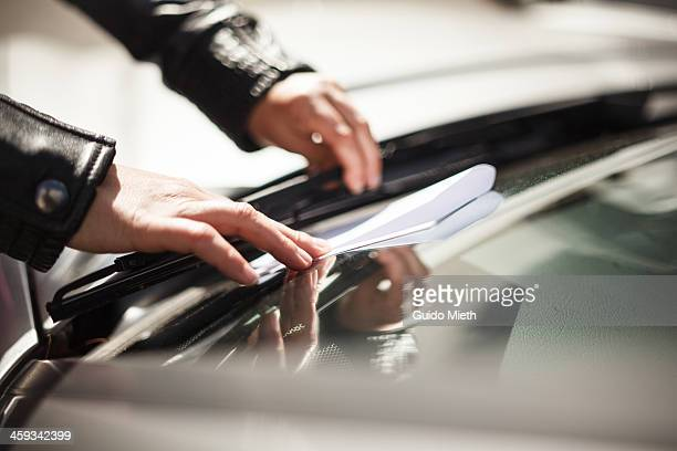 Hands placing a notice on windscreen
