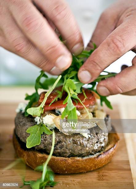 hands placing greens on burger - food state stock pictures, royalty-free photos & images