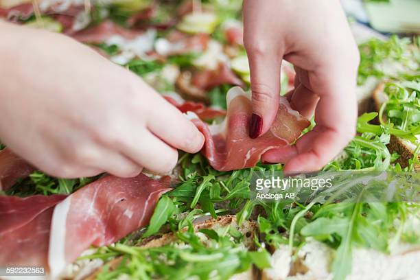 Hands placing meat slice on open faced sandwiches