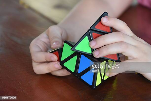 Hands playing a triangle cube game