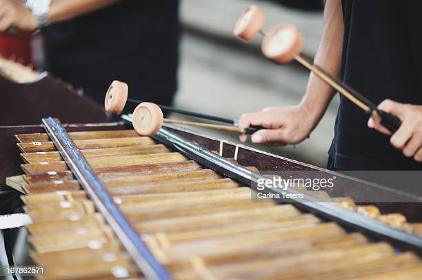 Hands playing a wooden xylophone