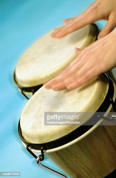 Hands playing bongo drums