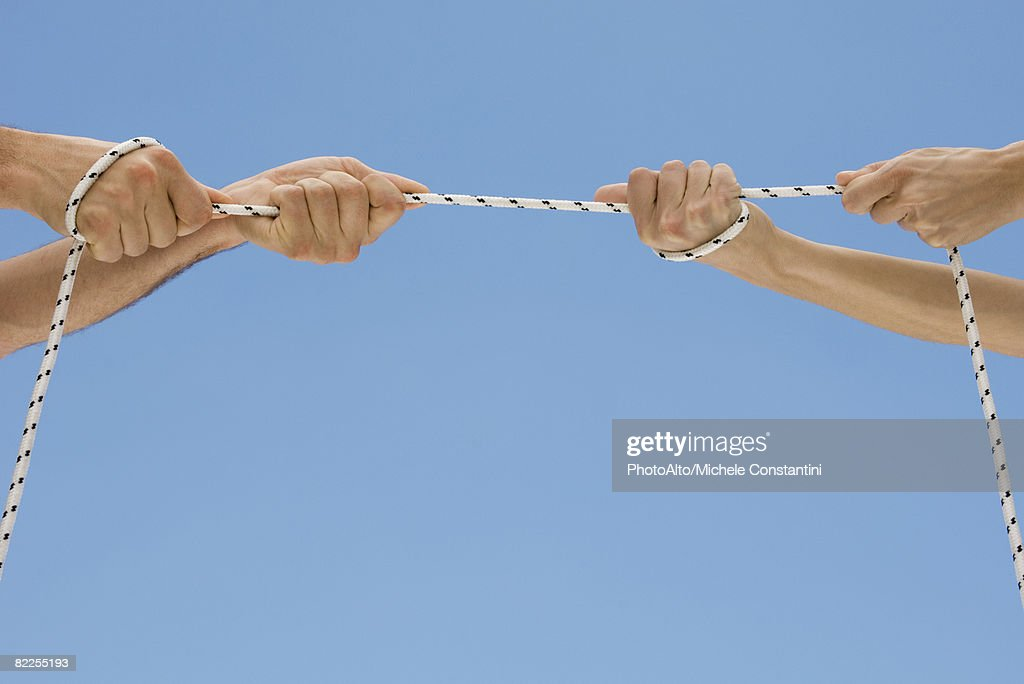 Hands playing tug-of-war with rope : Stock Photo