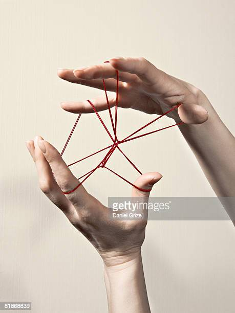 hands playing with a string