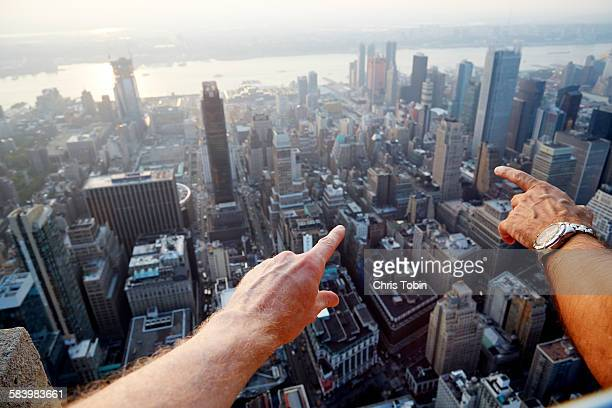 Hands pointing at city as seen from above