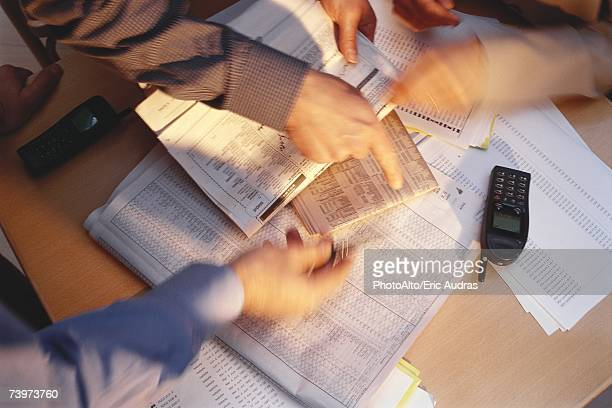 Hands pointing to financial pages of newspapers, blurred motion
