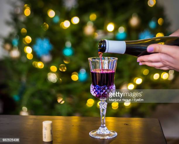Hands Pouring Wine In Glass On Table Against Defocused Lights