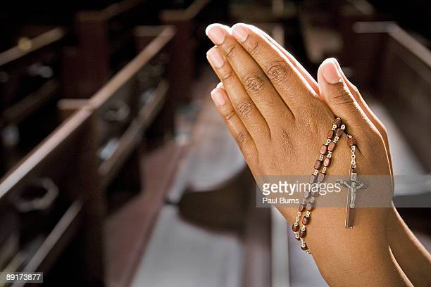 hands praying in church with rosary - religion stock pictures, royalty-free photos & images