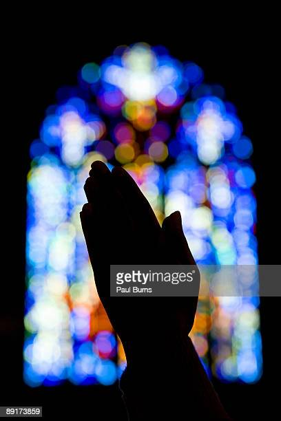 hands praying in church with stained glass - religion - fotografias e filmes do acervo