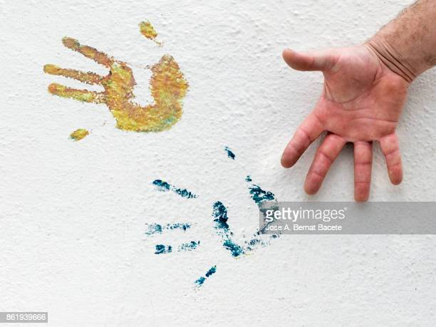 Hands Prints On Wall with colors, on a white wall in the street and the contrast of the open hand of a man