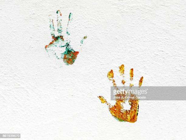 Hands Prints On Wall with colors, on a white wall in the street.
