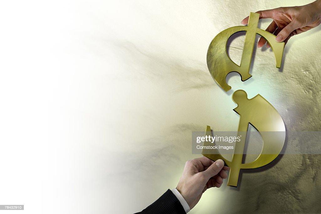 Hands pulling apart dollar sign : Stockfoto