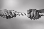 Hands pulling rope playing tug of war