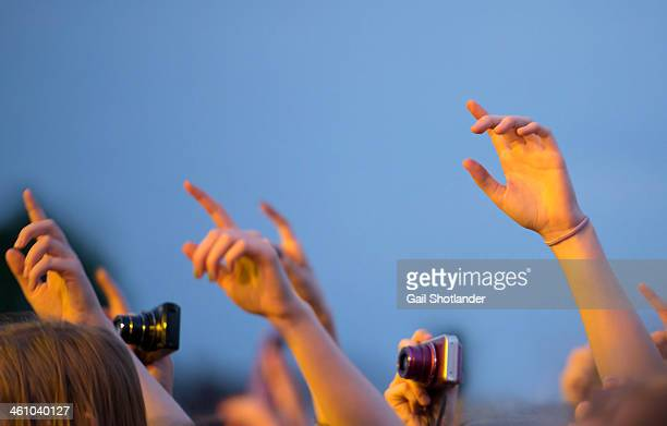 Hands pulse together with enjoyment during a concert. The image is of the forearms, hands, and cameras focused all to the left of the frame.