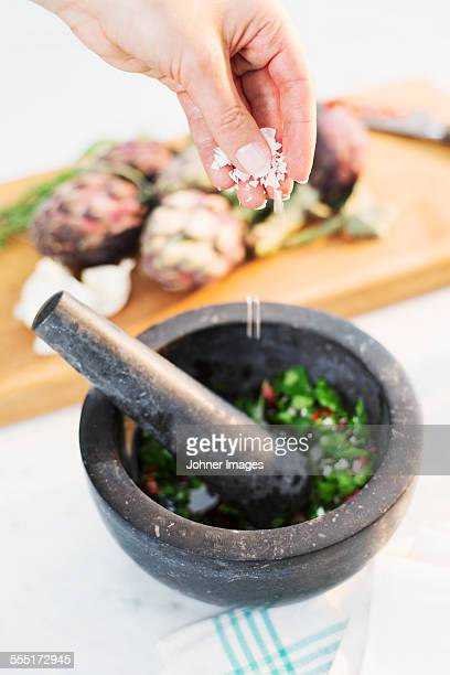 Hands putting spices into mortar