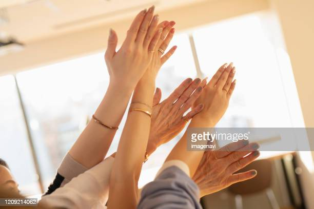 hands putting together - back of hand stock pictures, royalty-free photos & images