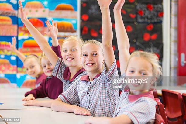 Hands Raised Smiling School Children in the Classroom