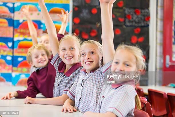 Hands Raised Smiling School Children in the Classroom