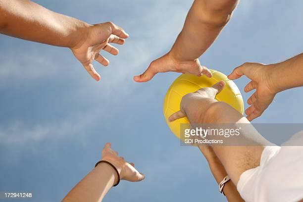 Hände greifen nach einem Volleyball geworfen in den blauen Himmel