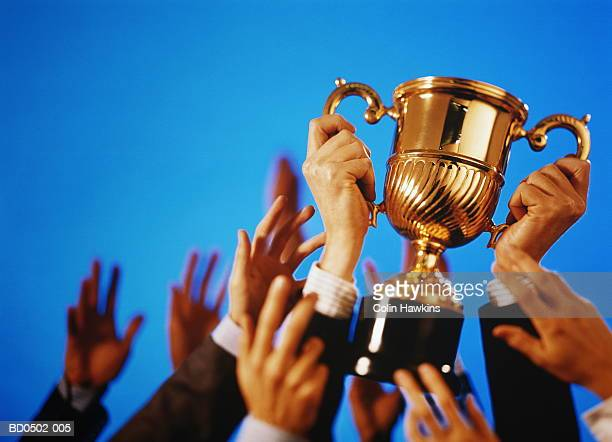 hands reaching for trophy (digital composite) - holding trophy stock pictures, royalty-free photos & images
