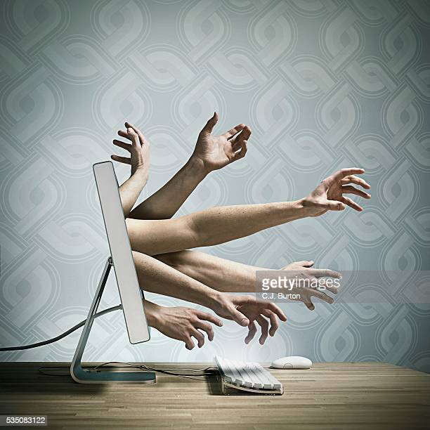 Hands reaching out of a computer screen