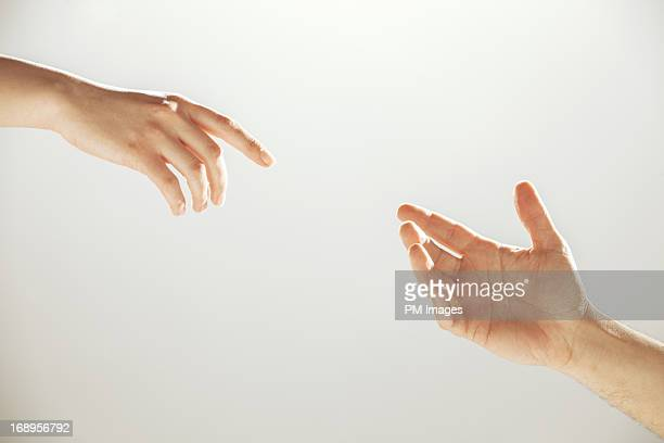 hands reaching towards each other - reaching stock pictures, royalty-free photos & images
