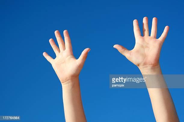 Mains pour atteindre sur ciel bleu en arrière-plan