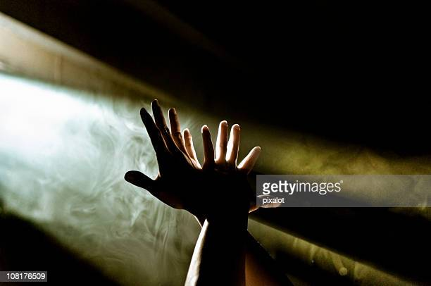 Mains pour atteindre jusqu'à rayon de lumière