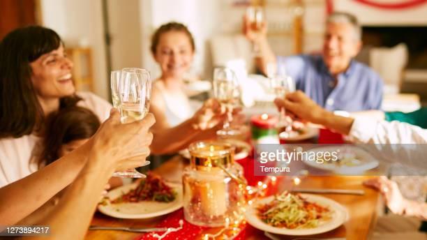 mani che alzano i flauti di champagne a cena di natale. - persona in secondo piano foto e immagini stock