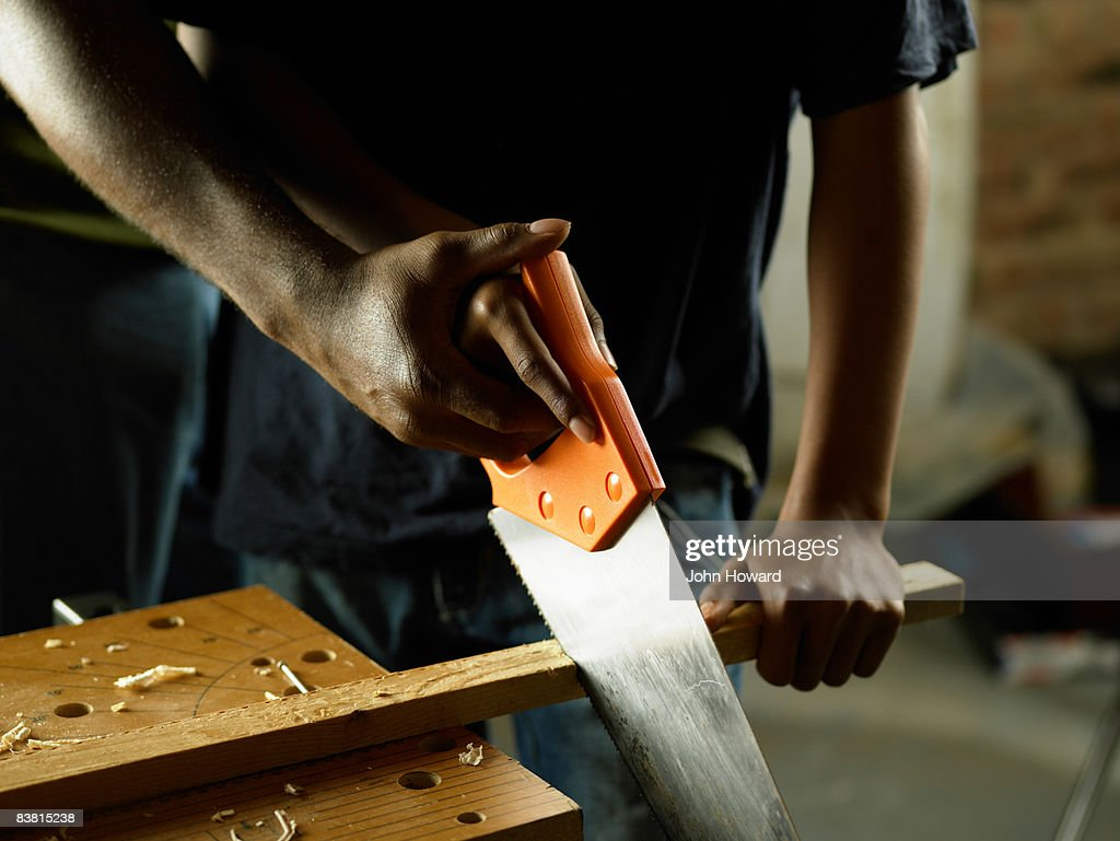 Hands sawing wood : Stock Photo