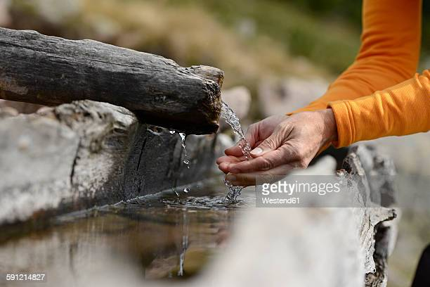 Hands scooping water from a well