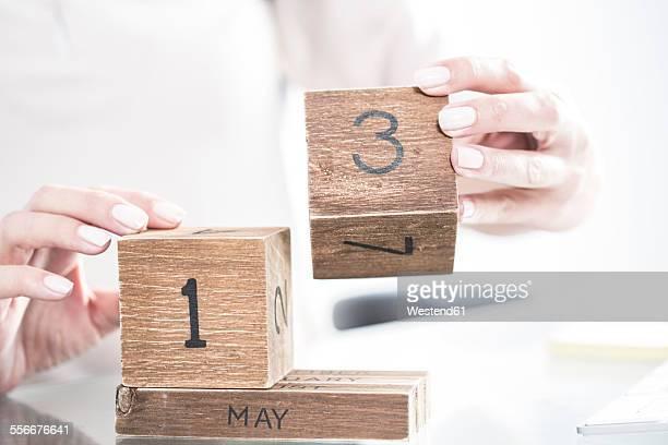 Hands setting the date on a wooden calendar