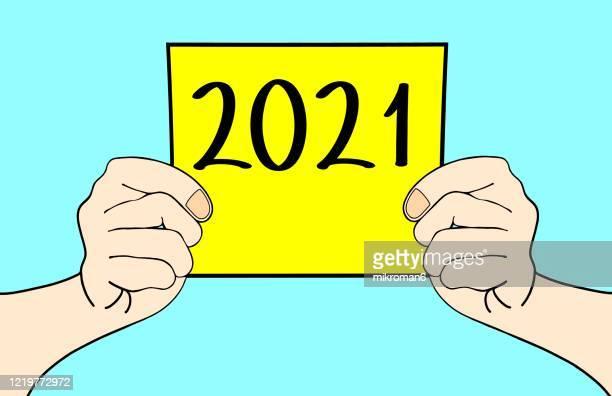 hands showing a paper page with 2021 - nieuwjaarsreceptie stockfoto's en -beelden