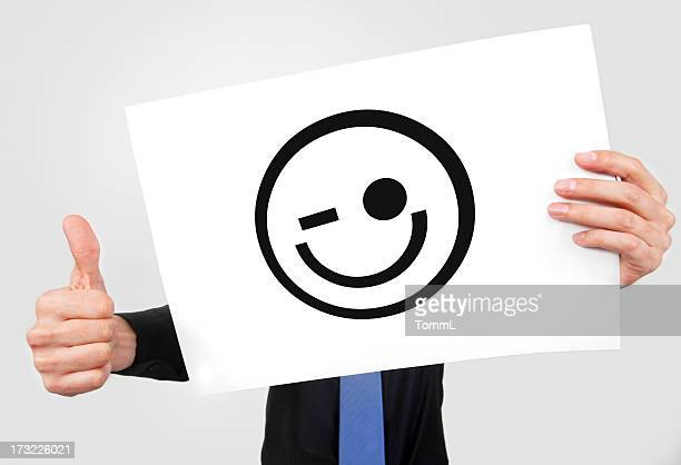 2 hands showing a smiley icon on a white paper & a thumb up