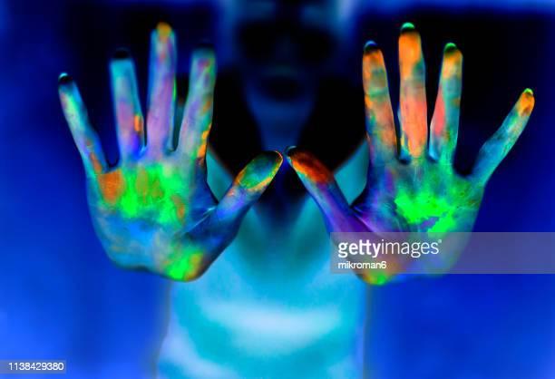 hands showing powder paint during party - fluorescerende stockfoto's en -beelden