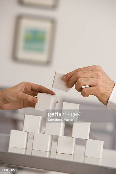 Hands stacking blocks