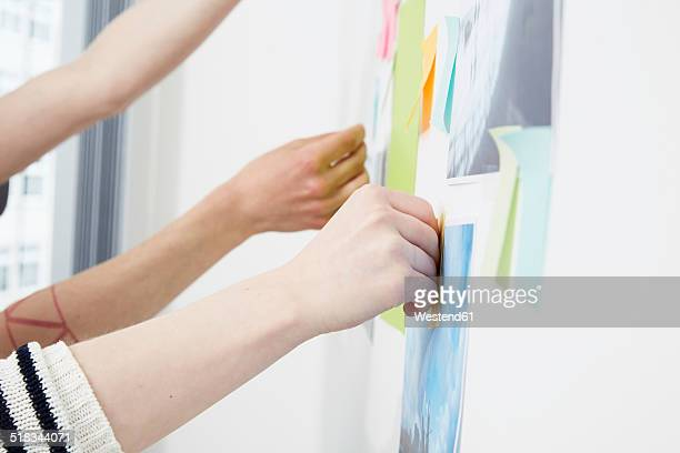 Hands sticking adhesive notes at wall