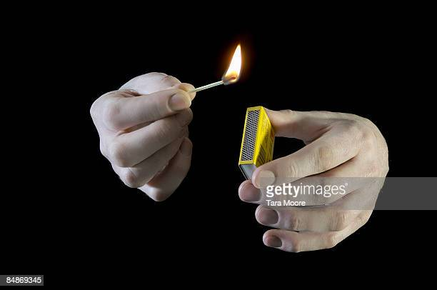 hands striking a match with match box - burning stock pictures, royalty-free photos & images