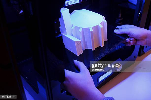 Hands taking a 3D building model from a 3D printer