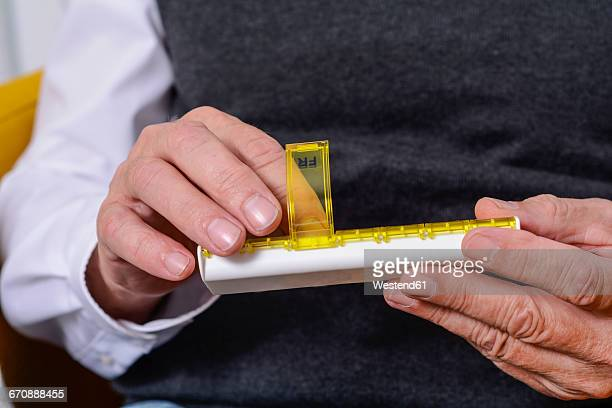 Hands taking pill from pill box