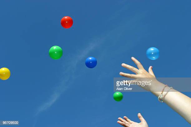 Hands throwing colored balls in the air