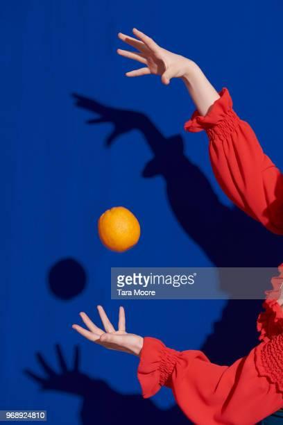 hands throwing orange in air - attività che richiedono movimento foto e immagini stock