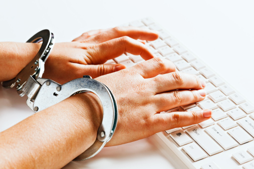 Hands tied unable to write freely on computer in handcuffs 155142534