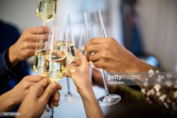 hands toasting champagne flutes during dinner party - champagne stock pictures, royalty-free photos & images