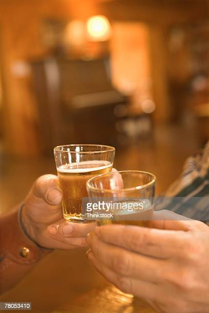 Hands toasting whiskey in saloon